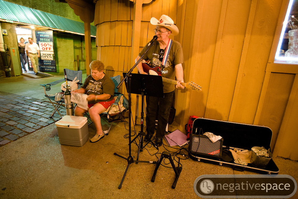 Old man street musician playing guitar and singing for his disabled wife, Fort Worth Stock Yards, Fort Worth, Texas