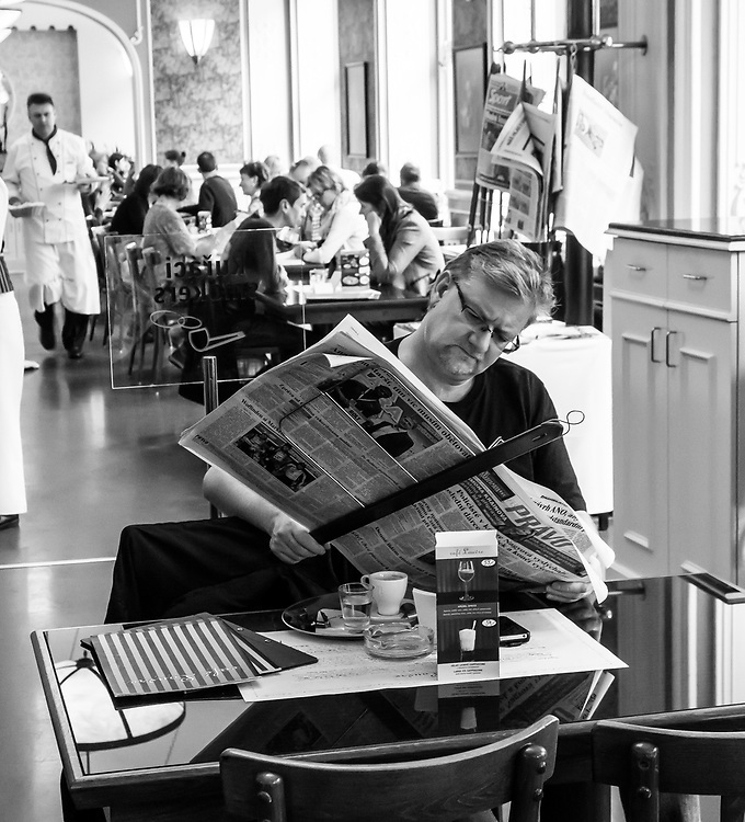 Sipping coffee and reading the newspaper at an elegant café. This gentleman enjoys these simple pleasures. Old and famous Cafe Louvre. Prague, Czech Republic.
