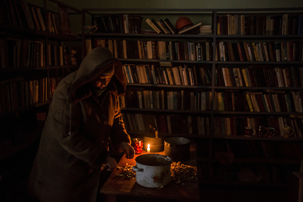 MYRONIVSKYI, UKRAINE - FEBRUARY 17: A woman cuts potatoes for a communal meal in the village library at the local House of Culture on February 17, 2015 in Myronivskyi, Ukraine. A ceasefire agreed to by Ukraine and pro-Russian rebel forces has failed to prevent fighting in the nearby town of Debaltseve, where thousands of Ukrainian troops remain and whom rebels claim to have surrounded. (Photo by Brendan Hoffman/Getty Images) *** Local Caption ***