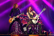 (L-R) Guitarist Dan Hawkins and frontman Justin Hawkins of The Darkness perform live on stage at HMV Hammersmith Apollo on November 25, 2011 in London, United Kingdom.  (Photo by Simone Joyner)