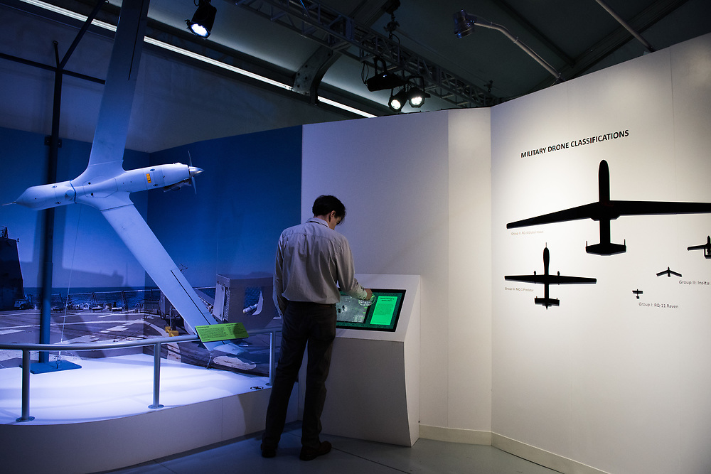 """30206010A - DRONES - An attendee looks at information about the Boeing Insitu ScanEagle drone next to a chart that shows the scale of different military drones at the """"Drones: Is the Sky the Limit?"""" exhibit at the Intrepid Sea, Air, and Space Museum in New York, NY on May 9, 2017."""