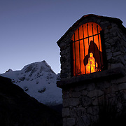Below the towering sentinel of Huandoy Este (East) 6,068m, the steep path to Pisco Base Camp passes a small shrine, where climbers cannot help but reflect on the fragility of life amongst the big mountains of the world.  Cordillera Blanca, Peru.  Nikon D200, 17-50/2.8.