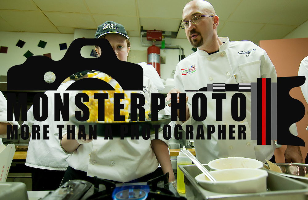 05/29/12 Wilmington Del: Chef Jim Berman (Right) assists Delcastle culinary student Brittany Bailey (16) with her sauté technique Tuesday May. 27, 2012, at Delcastle Technical High School in Wilmington Delaware. ..The News Journal/SAQUAN STIMPSON.
