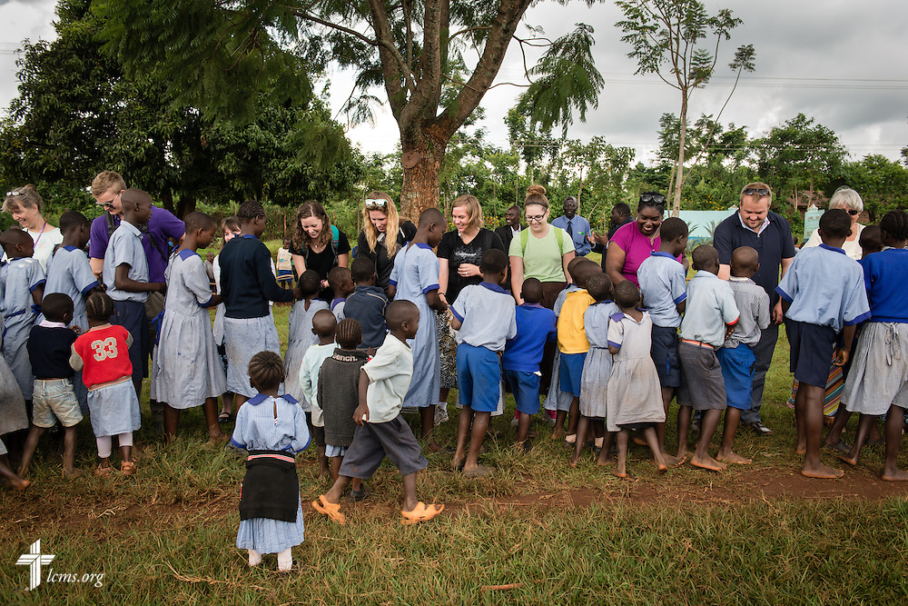 Members of the Mercy Medical Team greet approximately five hundred school children after arriving Monday, June 9, 2014, at the Luanda Doho Primary School in Kakmega County, Kenya. They are part of a 14-member Mercy Medical Team using a part of the school for a week-long medical clinic. LCMS Communications/Erik M. Lunsford