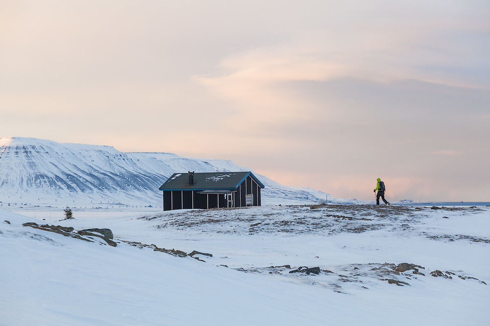 Nate Stevens approaches a backcountry cabin at the mouth of Foxdalen in Adventdalen, Svalbard.