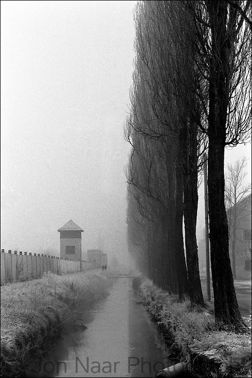 "Germany's first concentration camp viewed along a canal and row of trees in snow. Published in Jon Naar's ""Getting the Picture"" in 2005.  Taken with a 35 mm Leica M4."