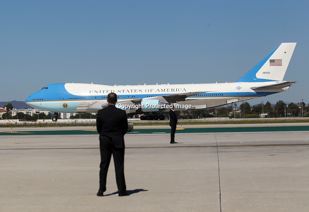 Security personnel stand as Air Force One, with President Barack Obama aboard, taxis at Los Angeles International Airport in Los Angeles on Saturday, Oct. 10, 2015. (AP Photo/Ringo H.W. Chiu)