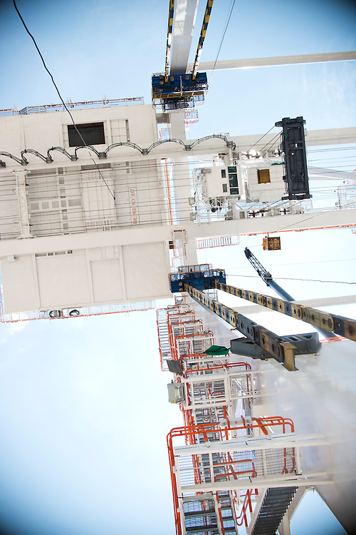(photo by Matt Roth).Wednesday, July 11, 2012.Assignment ID: 30128574A..A view from underneath one of the four super-post Panamax cranes -- the largest model built -- being erected at The Port of Baltimore's Seagirt Marine Terminal Wednesday, July 11, 2012. The blue jacking pods and the dangling blue and yellow jacking pod links are temporary structures used to elevate the trolly assembly...Once the building, testing and training is finished, the Seagirt terminal will join Norfolk, VA as one of the only two ports on the East Coast which can unload new Panamax sized container ships. The cranes are expected to be fully operational in September of this year.