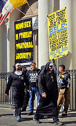 09 February 2016. New Orleans, Louisiana.<br /> Mardi Gras Day. Revelers dressed in habits pass fundamentalist Christians spewing messages of hate outside St Louis Cathedral in the French Quarter. <br /> Photo&copy;; Charlie Varley/varleypix.com