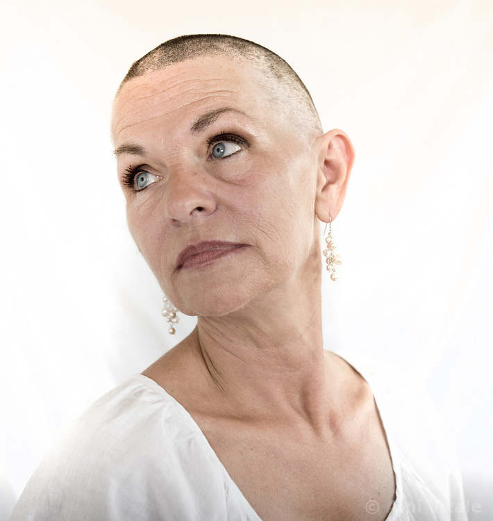 "Donna Branham of Lenore, West Virginia, poses after shaving her head on the steps of the West Virginia Capitol with a group of women in protest to mountaintop-removal mining. The shaving of their heads was symbolic of the mountains that have been stripped of all of the living things on them. It was also symbolic of the many people who are sick or dying as the result of Mountaintop Removal. Mountaintop Removal is a method of surface mining that literally removes the tops of mountains to get to the coal seams beneath. It is the most profitable mining technique available because it is performed quickly, cheaply and comes with hefty economic benefits for the mining companies, most of which are located out of state. It is the most profitable mining technique available because it is performed quickly, cheaply and comes with hefty economic benefits for the mining companies, most of which are located out of state. Many argue that they have brought wage-paying jobs and modern amenities to Appalachia, but others say they have only demolished an estimated 1.4 million acres of forested hills, buried an estimated 2,000 miles of streams, poisoned drinking water, and wiped whole towns from the map. ""People don't know how hard it is on the Appalachian people,"" Branham said of mountaintop-removal mining. ""They have no idea. And they don't want to know. As long as they don't have to look at it, they can ignore it."" © Ami Vitale"