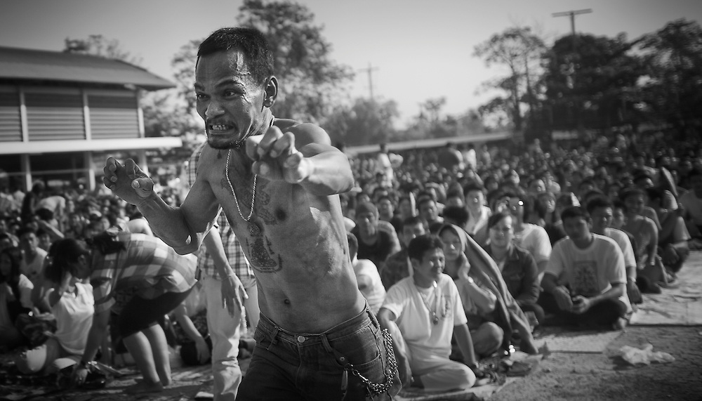 "A devotee works himself into a frenzy during the annual ""Wai Kru"" tattoo festival at Wat Bang Pra in Nakhon Chasi, Thailand Saturday, March 23, 2013. Devotees attend the one day event to have their ""Sak Yant"" religious tattoos energized by Buddhist monks and tattoo masters."