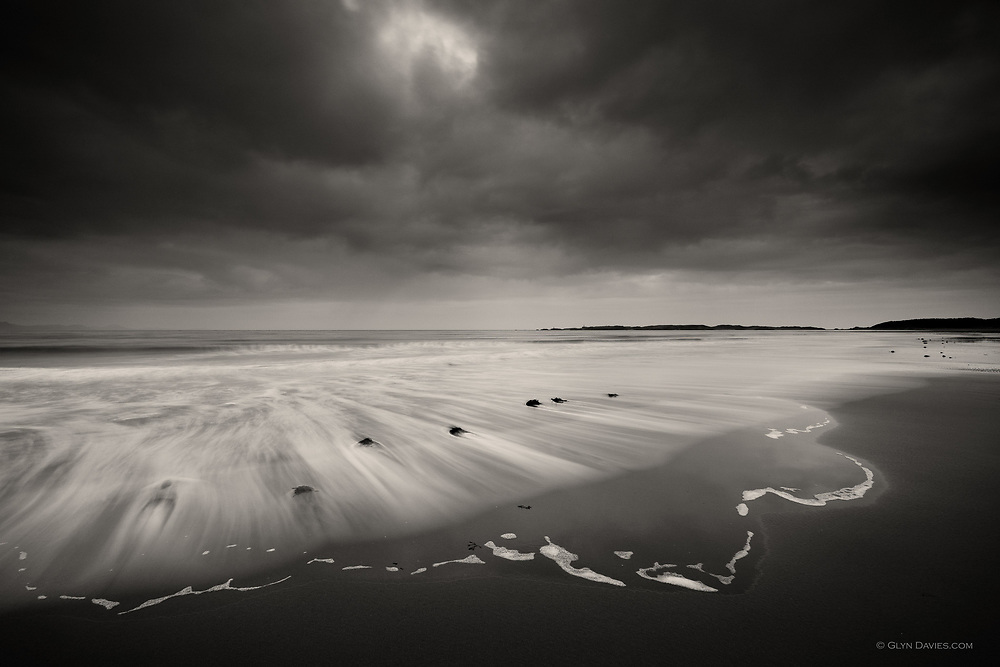 Nominated for 11th International B&amp;W Spider Awards<br /> <br /> Shot on Llanddwyn beach as everyone else was leaving - well it was a bitter cold evening, no sunset, no 'obvious' excitement, but I was utterly connected that evening. In the darkness and solitude I became one with the peace, the dusk, the gentleset lapping sounds at the shore, the occassional oystercatcher calling as it skimmed the sea. I photographed gentle events...&copy; Glyn Davies 2012  All rights reserved. No copying or use on any website is either permitted or implied. Action WILL be taken against infringers.