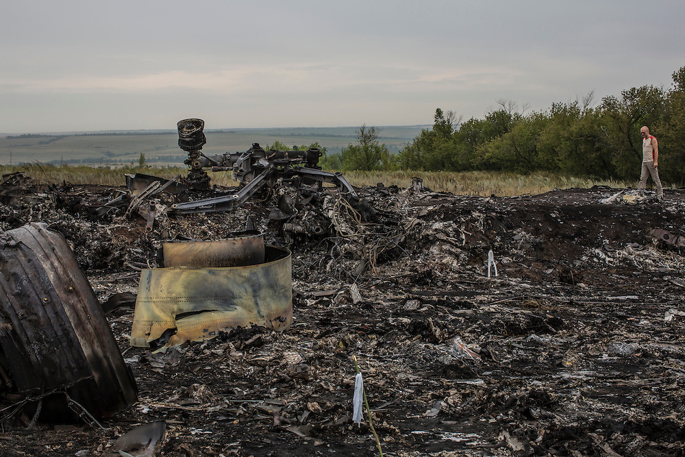 GRABOVO, UKRAINE - JULY 18: A man looks at debris from an Air Malaysia plane crash on July 18, 2014 in Grabovo, Ukraine. Malaysia Airlines flight MH17 travelling from Amsterdam to Kuala Lumpur has crashed on the Ukraine/Russia border near the town of Shaktersk. The Boeing 777 was carrying 280 passengers and 15 crew members. (Photo by Brendan Hoffman/Getty Images) *** Local Caption ***