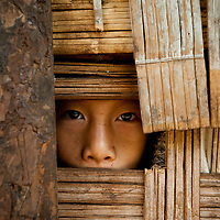 Stilted village dwellings in northern rural Thailand are literally constructed out of bamboo and little else. This little girl had found a peephole at the perfect height to observe visitors.