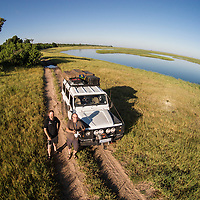 Africa, Botswana, Chobe National Park, Aerial view of photographers Paul Souders and Edwin Remserg by Land Rover Defender along Chobe River in Okavango Delta