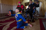Wounded Wael al-Namlah, 26, and his wife Asraah as  their three year-old son Sharif  crawls on the carpet at their home in Rafa,Gaza January 20,2015. Wael lost one of his legs, his wife lost both and their son lost one leg during last summer's war between Israel and the Hamas-controlled Gaza Strip. The incident happened on one of the darkest days during the war that has been named 'Black Friday'. Palestinians claim 130-150 were killed in the Rafa area of southern Gaza during a breakdown of a ceasefire agreement during a tunnel incident between Hamas and Israeli troops .<br /> The family was fleeing on foot trying to reach a safer area when an Israeli  rocket attack hit them . Wael's 11 -year old sister and his brother Yusef and his wife were killed . (Photo by Heidi Levine/Sipa Press).