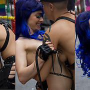 Amy Sales  and girl friend affectionately playfully hugging both semi-nude and bare breasted.  Amy (lesbian dominatrix) wearing a purple wig holding a whip, her girl friend dressed in S&amp;M leather gear before the start of the Pride Parade in NYC.<br />