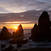 The sun sets behind one of the prominent sea stacks known as the Marin Headlands at Rodeo Beach, located in the Golden Gate National Recreational Area near San Francisco, California.
