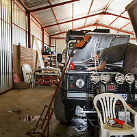 South Africa, Mechanic climbs onto hood of Land Rover Defender safari truck while repairing hydraulic system in garage