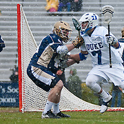Duke midfielder Jake Tripucka #7  drives on Quinn Cully Midfield #41. The third-ranked Fighting Irish defeated sixth-ranked Duke, 13-5, in men's lacrosse action on a snowy Saturday afternoon at Koskinen Stadium in Durham, N.C.