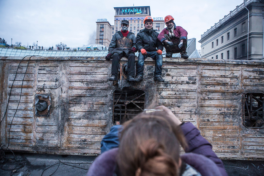 KIEV, UKRAINE - FEBRUARY 20: Anti-government protesters pose for a photo on top of a burned and overturned bus on Independence Square on February 20, 2014 in Kiev, Ukraine. After several weeks of calm, violence has again flared between anti-government protesters and police, with dozens killed. (Photo by Brendan Hoffman/Getty Images) *** Local Caption ***