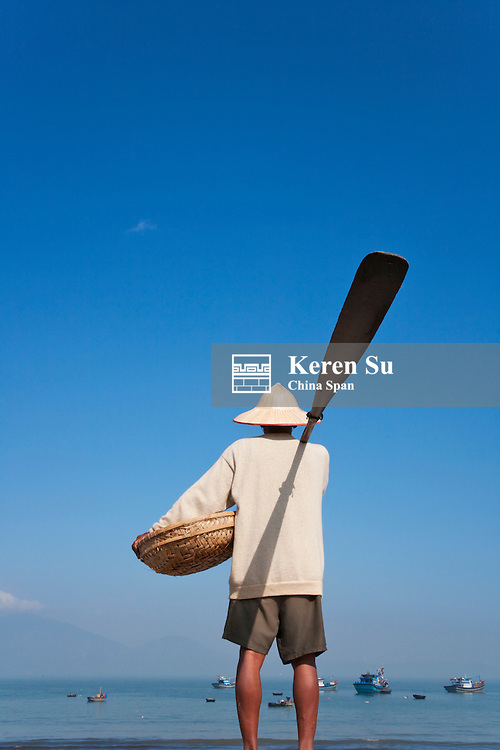 Fisherman with paddle and basket on China Beach.