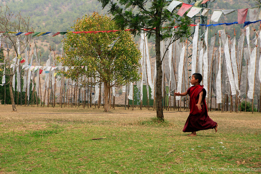 Asia, Bhutan, Punakha. Young monk and prayer flags at Chimi Lhakhang.