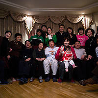 BEIJING, 25. JANUARY, 2009 :   Mr. Li (C) , a paper factory owner, and his relatives pose for a family picture  on new years' eve  in Beijing .<br /> Mr. Li, a paper factory owner, is facing one of his most difficult times .&quot; Last November the market suddenly went down ,&quot; Li says.   <br /> He had bought paper, a lot of paper, and paid 7000 Yuan/ t .<br />  Li's company buys paper from paper mills and lives from the sales to publishing houses and other companies.  Since the market's collapse , he manages to sell the paper only for 6000 Yuan/t.<br /> His clients' export business to the USA had shrunk in Southern China. Mobile phone manufacturers don't need paper for the instruction guides to their mobile phones anymore as their US clients buys less China- made mobile phones.<br />  Toy manufacturers don't need paper anymore  because Americans import less toys from China. &quot; The crisis has driven many of my clients into bancruptsy&quot;, says Li.<br />  <br /> China's Communist Party  which will celebrate its 60th anniversary in October, currently faces its biggest challenge since the beginning of the economic reforms 30 years ago  : &quot; The phase of  rapid economic growth is over. For the first time the government is threatened with a  mistrust of a wide section of the population&quot;, warns the Communist party's Shang Dewen in Beijing.   <br /> Not only the China's poorest worry about the furture, but as well China's middle class is concerned about the crisis.     1,5 Millionen university graduates didn't find a job until the end of 2008  and this summer there'll be an additional  6,1 Million new graduates. More than 12 percent of university graduates face unemployment in 2009.