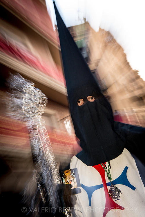 """La Trinidad Brotherhood in the evening of Holy Saturday walk in a central street in Sevilla. Here """"Nazarenos"""", dressed with a black """"capirote"""", the peculiar conical hat, and a white tunic  perform their penance carrying along the procession either long (and heavy) Paschal candles or wooden crosses."""