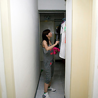 BEIJING, JULY -21.2010 : A YOUNG WOMAN LOOKS FOR HER CLOTHES IN THE COMMUNITY CABINET IN THE HALLWAY OF A BASEMENT .