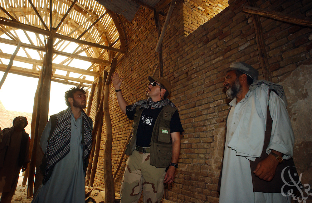 U.S. Army Maj. Phil Williams (C), of the 489th Civil Affairs Battalion from Knoxville, TN, discusses the progress of a grain silo construction with local Afghan contractors June 08, 2002 in Kunduz, Afghanistan. Williams and others from the 489th have overseen a number of humanitarian projects recently, including the construction of a school for 4,000 Afghan girls and the reconstruction of the Teachers' College, as part of the ongoing Operation Enduring Freedom.