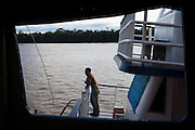 Meandering the Rio Amazonas, Avenger II picks up a boat in need of towing to a repair yeard. The Avenger III is a passenger ship making the twice a month journey from the frontier town of Tabatinga in the Tr&ecirc;s Fronteiras region of Northwestern Brazil, to the capital of the State of Amazonas, Manaus. It&rsquo;s also where the Rio Amazonas enters Brazil from its source in neighboring Peru. <br /> <br /> Carrying passengers and crew totaling almost 200 and small cargo, the ship meanders its way along the Rio Amazonas and Rio Solimoes for four days and three nights. Stopping at half a dozen or so makeshift ports en-route, the service provides a vial link for communities along the river to get products to the city and more importantly, in the absence of roads or airfields, provide a means for the sick to reach care in the city of Manaus.<br /> <br /> For those not fortunate to be accommodated in one of the two or three cabins available, home is space found for a self supplied hammock amongst the kaleidoscopic web of coloured fabrics. <br /> <br /> By the second day, negotiating a stroll from port to starboard can seem more like negotiating an assault course of tangled ropes and personal baggage deliberately piled high to protect ones personal space.<br /> <br /> Food served three times daily is adequate, a staple of soups, chicken, rice and noodles. An &lsquo;entertainment&rsquo; deck on the top floor provides ample opportunity to be social engaging in card and board games with beer swilling, chain smoking locals.