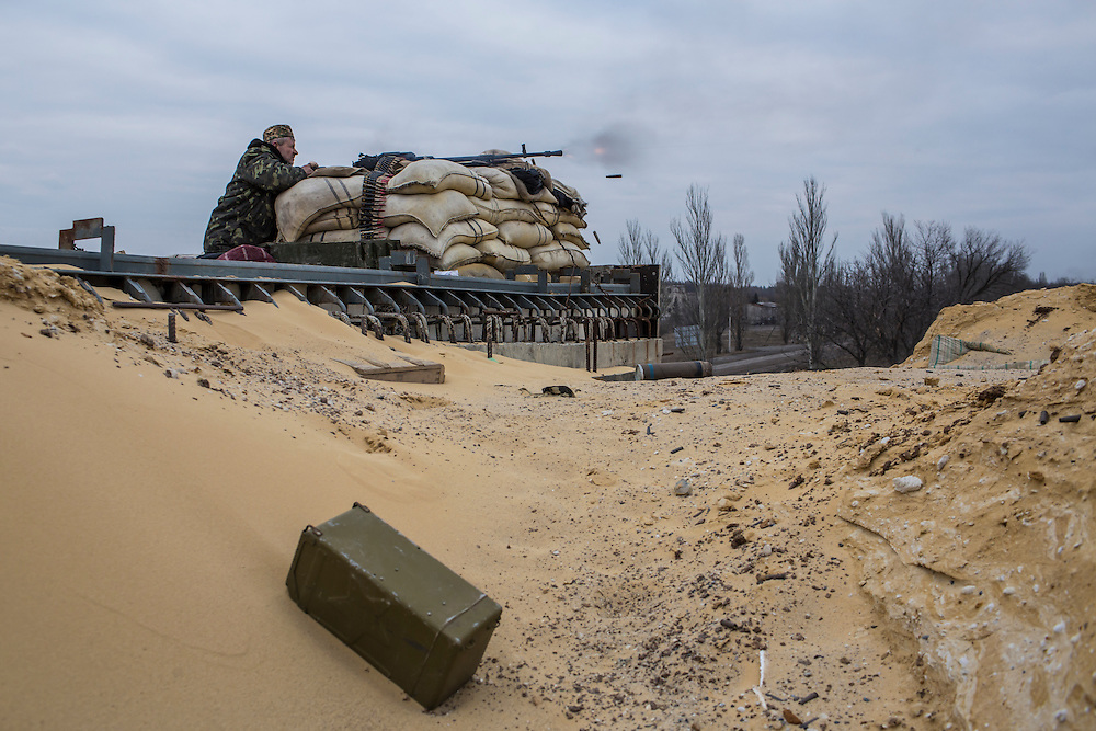 PERVOMAISKE, UKRAINE - MARCH 19, 2015: A fighter who uses the name Uncle Vova, a member of the pro-Ukrainian Dnipro-1 battalion, fires a gun toward pro-Russian rebel positions from one of the group's bases known as The Bridge near ongoing battles for the town of Pisky in Pervomaiske, Ukraine. CREDIT: Brendan Hoffman for The New York Times