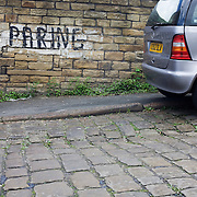 A car has been parked on cobbles by a hand-painted sign that urges no parking at the kerbside in a quiet street near Bradford city centre, Yorkshire.