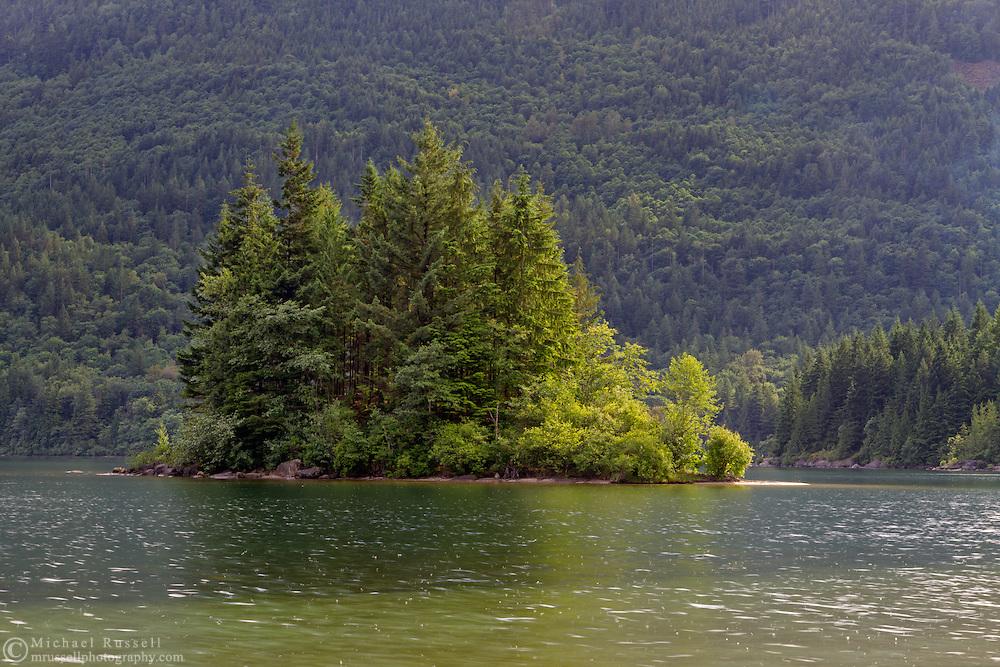 Sunshine illuminates the trees on a small island in Hicks Lake at Sasquatch Provincial Park, British Columbia, Canada