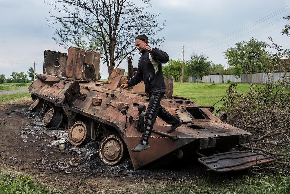 OKTYABRSKAYA, UKRAINE - MAY 14: A man leaps off  a destroyed armored personnel carrier on May 14, 2014 in Oktyabrskaya, Ukraine. Pro-Russian militants ambushed Ukrainian troops nearby the day before, killing seven and wounding another eight in the most deady attack yet on Ukrainian forces. (Photo by Brendan Hoffman/Getty Images) *** Local Caption ***