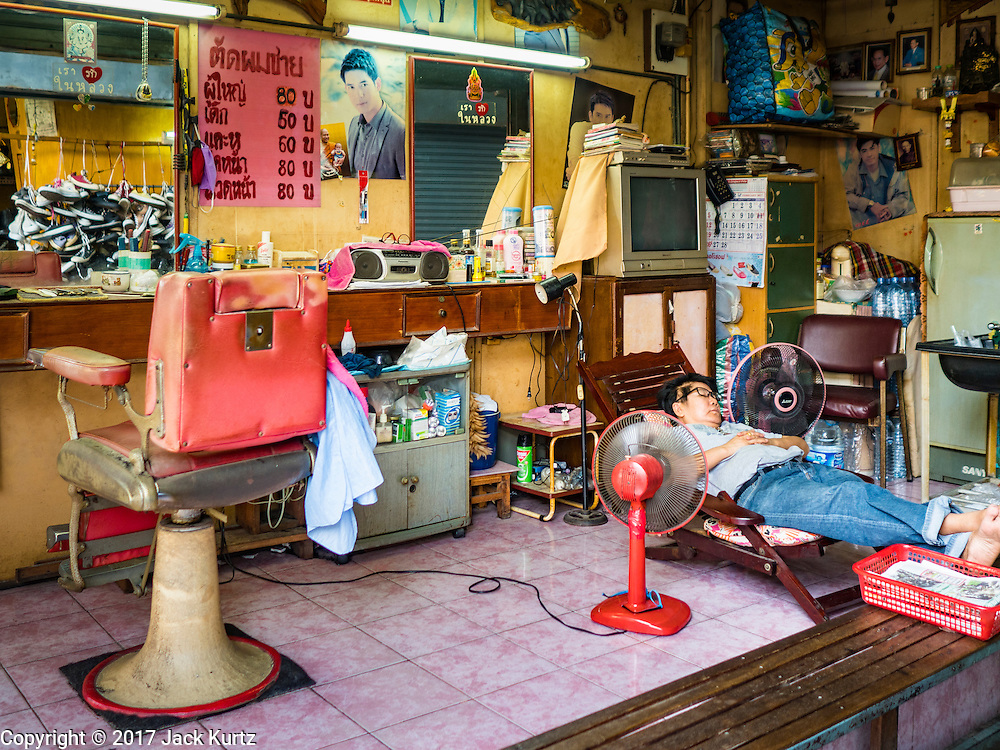 "06 FEBRUARY 2017 - BANGKOK, THAILAND: A barber naps while waiting for customers in his shop in what used to be known as Kalabok Market under the Phra Khanong Bridge in the Phra Khanong district of Bangkok. Kalabok is the Thai word for hairdresser and the market was called Kalabok because there were many barbershops and hairdressers under the bridge. In 1985, the city changed the name of the market to ""Singha Market."" There are still about 10 small men's barbershops, most with just one barber, and four women's salons, most with one hairdresser,  under the bridge.      PHOTO BY JACK KURTZ"