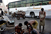On the edge of Dharavi where the slum meets one of Bombays main roads, men take their early morn wash. The kerosene cow man can be seen taking cooking fuel to sell to the resisdents of Dharavi. Kerosene remains, as for most of India, the fuel of choice to cook with.