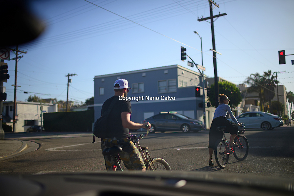 Bicycle riders waiting for streetlight, view from inside a car, Venice, California.