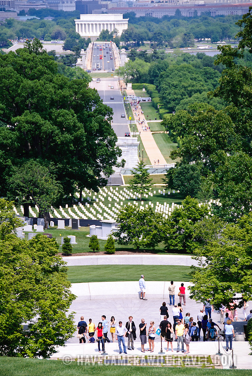 Tourists at John F. Kennedy's gravesite at Arlington Cemetery (foreground) with Memorial Bridge and the Lincoln Memorial in the background. View from Arlington House.