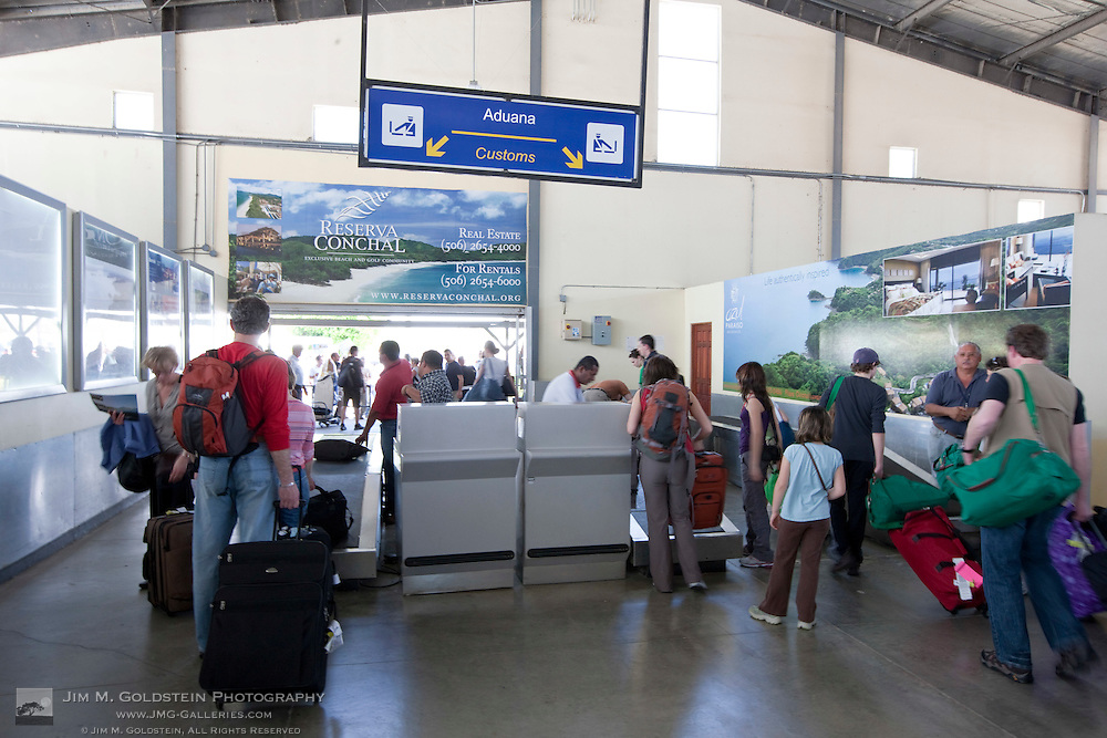 Tourists have their luggage inspected by customs at the Liberia airport in Costa Rica.