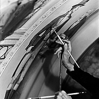 Capitol muralist Cliff Young used a mahl stick to steady his hand while filling in details on the ceiling of a hallway in the U.S. Capitol.