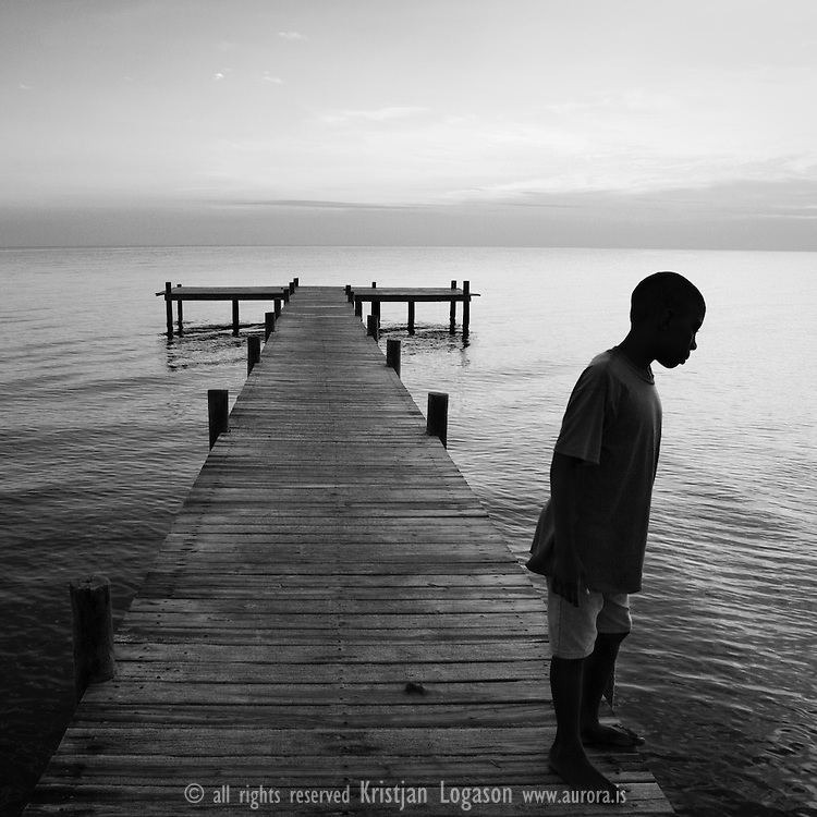 young boy standing on the jetty in central Hopkins in Belize, at sunset lokking for fish and manatee