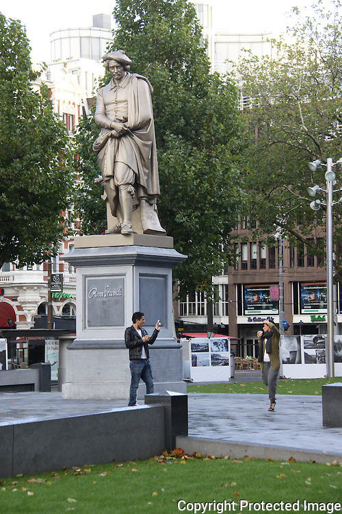 Man photographing girlfriend in front of Rembandt statue in Rembrandplein