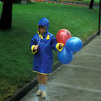 A sad little girl walks in the rain with her balloons.