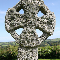 Granite Celtic Cross covered with lichen St Michael's Church, Caerhays, Goran, Cornwall, UK