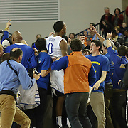Delaware Students rush the court to celebrate with Delaware Guard Davon Usher (0) and the Men's basketball team after The Hens come from down 20 points to defeat The College of Charleston 67-64 in a Colonial Athletic Association conference game Wednesday, Feb 5, 2014 at The Bob Carpenter Sports Convocation Center in Newark Delaware.