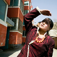 TONGREN, APRIL 4, 2012 : a Tibetan woman  stands next to a settlement for nomads created by the local government.