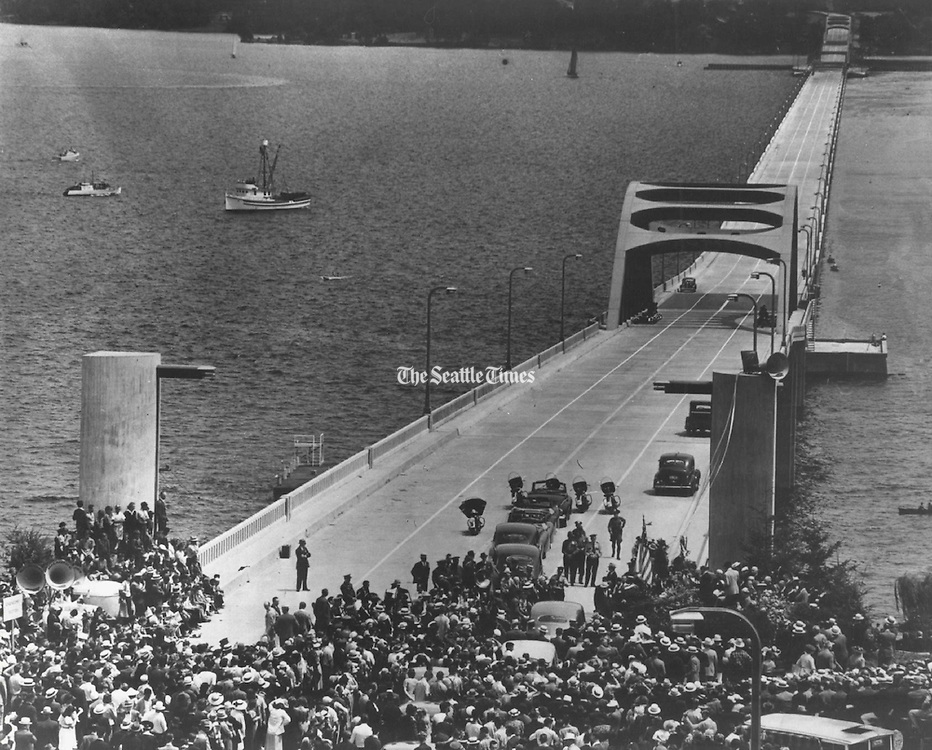 With 2,000 persons crowded around the speaker's stand at the west end of the new Lake Washington Floating Bridge, and other thousands gathered at the east end and along the lake shores, the new bridge was dedicated and opened to traffic. (Hack Miller / The Seattle Times, 1940)