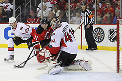 Apr 7; Newark, NJ, USA; New Jersey Devils right wing Stephen Gionta (11) beats Ottawa Senators defenseman Erik Karlsson (65) for the puck in front of Ottawa Senators goalie Craig Anderson (41) during the first period at the Prudential Center.